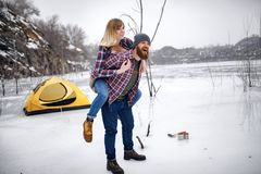 Young couple has fun during winter hike. Young couple has fun during winter hike against background of ice, rocks and yellow tent stock image