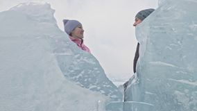 Young couple has fun during winter walk against background of ice of frozen lake. Love story. Lovers hide behind the ice. Young couple has fun during winter walk stock footage