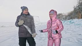 Young couple has fun during winter walk against background of ice of frozen lake. Love story. Lovers keep an ice floe. Young couple has fun during winter walk stock footage
