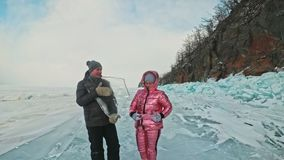 Young couple has fun during winter walk against background of ice of frozen lake. Love story. Lovers keep an ice floe. Young couple has fun during winter walk stock video footage