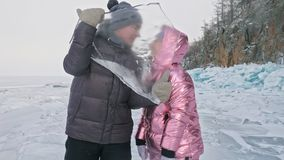 Young couple has fun during winter walk against background of ice of frozen lake. Love story. Lovers keep an ice floe. Young couple has fun during winter walk stock video