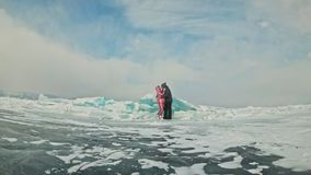 Young couple has fun during winter walk against background of ice of frozen lake. Lovers are having fun, laughing. Jumping, kissing near a huge blue ice floe stock video footage