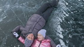 Young couple has fun during winter walk against background of ice of frozen lake. Lovers lie on clear ice with cracks. Have fun, kiss and hug. View from above stock footage