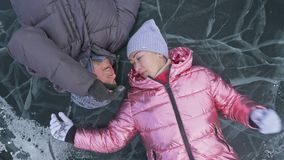 Young couple has fun during winter walk against background of ice of frozen lake. Lovers lie on clear ice with cracks. Have fun, kiss and hug. View from above stock video