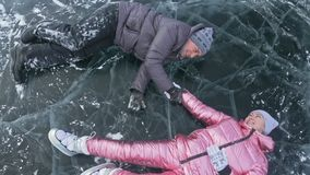 Young couple has fun during winter walk against background of ice of frozen lake. Lovers lie on clear ice with cracks. Have fun, kiss and hug. View from above stock video footage