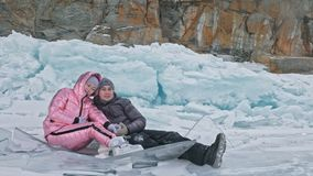 Young couple has fun during winter walk against background of ice of frozen lake. Lovers sit on ice, kiss and hug. Young. Happy people stroll through the snow stock footage