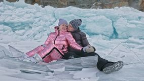 Young couple has fun during winter walk against background of ice of frozen lake. Lovers sit on ice, kiss and hug. Young. Happy people stroll through the snow stock video