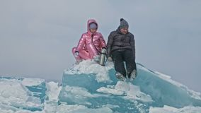 Young couple has fun during winter walk against background of ice of frozen lake. Lovers are sitting on large blue ice. Young couple has fun during winter walk stock video footage