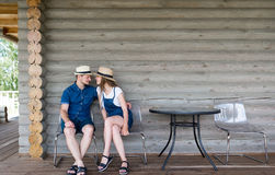 Young couple in hats against the background of a wall of the wooden house stock image