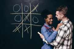 Young couple have fun leisure, play tic tac toe Royalty Free Stock Photo