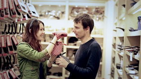Young couple have fun in mall. Kitchen potholder