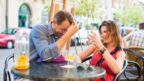 Young couple have a great time in cafe with mobile phone. Royalty Free Stock Image