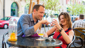 Young couple have a great time in cafe with mobile phone. Royalty Free Stock Images