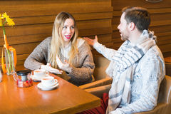 Young couple have interesting discussion in cafe Royalty Free Stock Images
