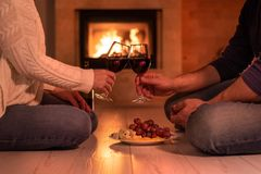 Young couple have romantic dinner with wine over fireplace background. royalty free stock photo
