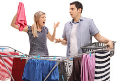 Young couple having an argument while hanging clothes. On a clothing rack dryer isolated on white background Royalty Free Stock Photography