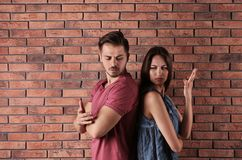 Young couple having argument near brick wall. Relationship problems stock image