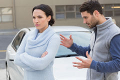 Young couple having an argument. Outside their car Stock Photos