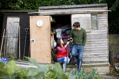 A young couple having a break on an allotment, drinking wine Royalty Free Stock Photos
