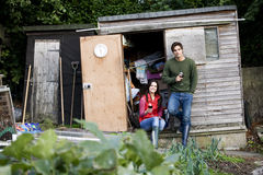 A young couple having a break on an allotment, drinking wine Royalty Free Stock Images