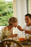 Young couple having breakfast. Young man and woman sitting at the breakfast table Royalty Free Stock Photos