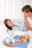 Young couple having breakfast in bed Stock Photos