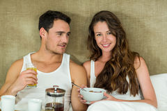 Young couple having breakfast on bed Stock Images