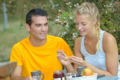 Young couple having breakfast outdoors royalty free stock photography