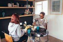 Couple having breakfast together at home. Young couple having breakfast together at home. African men with girlfriends sitting around dining table eating Royalty Free Stock Image