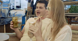 Young couple having coffee cocktails in cafe. Young man and woman sitting in outdoor beach cafe. They clanging glasses and relaxing with drinking coffee stock video