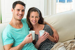 Young couple having coffee on sofa Stock Photos