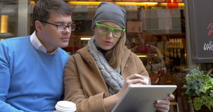 Young couple having coffee and using pad in city. Young cheerful man and woman sitting on the bench by the cafe. They drinking coffee, using tablet computer and stock video