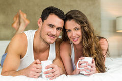 Young couple having cup of coffee on bed Royalty Free Stock Photo