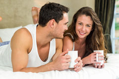 Young couple having cup of coffee on bed Stock Image