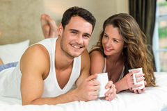 Young couple having cup of coffee on bed Royalty Free Stock Photography