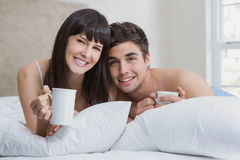 Young couple having cup of tea on bed Stock Image