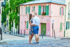 Young couple having a date on Montmartre, Paris, France. Young romantic couple having a date on a street of Montmartre and kissing near a pink house in Paris Stock Photos
