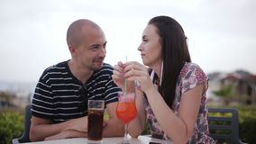 Man and woman drinking cocktails in a cafe outdoors. Young couple is having a date, they are sitting in outdoor cafe in sunny day and drinking cocktails stock video footage