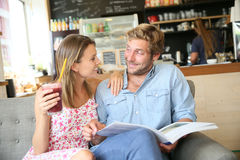 Young couple having a drink reading magazine Stock Photography