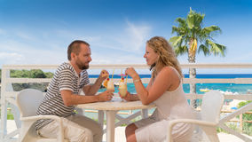 Young couple having a drink on a terrace at a sea Stock Images