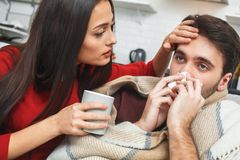 Young couple having evening at home girlfriend taking care close-up. Young men and women evening indoors girlfriend taking care of sick boyfriend with cold runny royalty free stock images