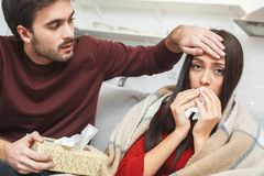 Young couple having evening at home husband taking care. Young men and women evening indoors husband taking care of ill wife with rheum holding tissue looking royalty free stock image