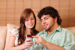Young couple having fun. Young couple sitting on a couch, pointing at and having fun with a mobile telephone royalty free stock photography