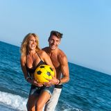 Young couple having fun with ball on beach. Stock Images