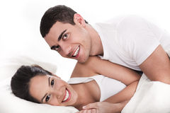 Young couple having fun in bed. Over white background Stock Photos