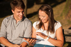 Young couple having fun on a bench in park while socializing ove Stock Image