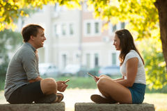 Young couple having fun on a bench in park while socializing ove Stock Photo