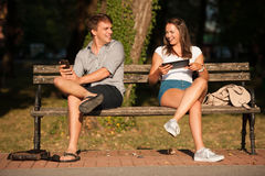 Young couple having fun on a bench in park while socializing ove Royalty Free Stock Photography