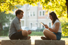 Young couple having fun on a bench in park while socializing over web stock photography