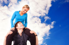 Young couple is having fun (blue sky background).  royalty free stock photo
